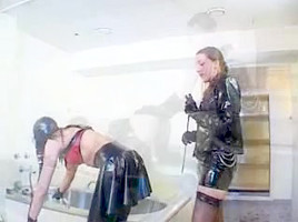 Hot brunette mistress in latex fists her slave